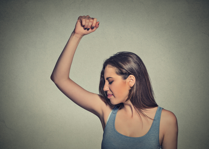woman with raised fist smelling her armpit