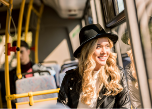 young blonde woman sitting on a bus doing a kegel workout