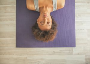 woman lying on a yoga mat focused in her exercise