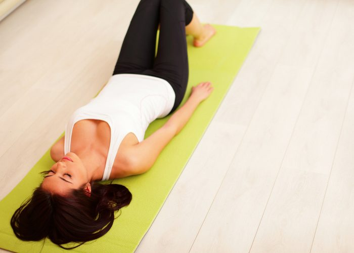 young woman lying on yoga mat doing a kegel workout