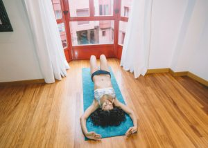 woman lying on a yoga mat in front of bay windows doing pelvic exercises
