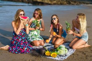 Four women in colourful dresses sitting on the beach enjoying fruits