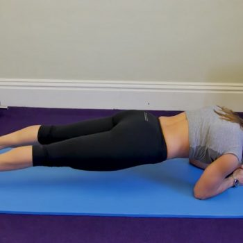 Woman exercising on the floor i plank position in the middle of a lower ab exercises workout