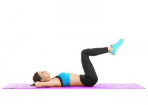 woman lying on an exercise mat on the floor doing heel touches for abs workout