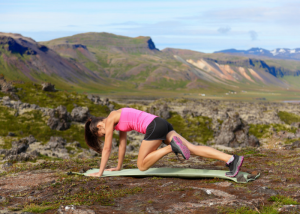 woman outdoors on an exercise mat in the mountains doing mountain climber exercises