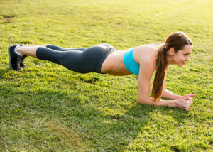 woman doing planks on a green lawn to tone lower abs