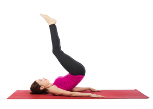 woman lying on exercise mat doing reverse crunch lower ab exercises