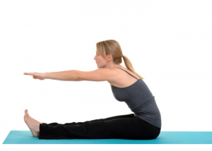 woman sitting on an exercise mat reaching for her toes