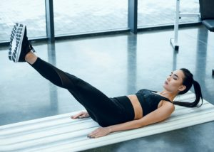 woman lying on exercise mat doing straight leg holds to tone lower abs