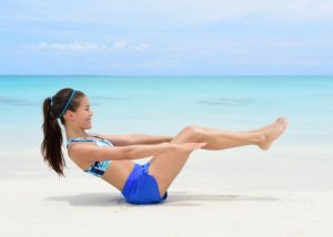 woman doing v sits lower ab exercises on a beach