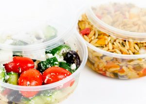 meal delivery containers filled with greek salad and orzo pasta