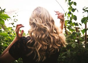 woman with luscious long hair standing among plants