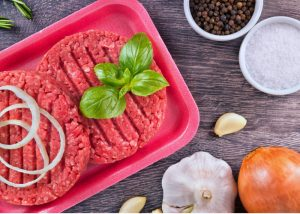 meal kit of 2 fresh burger patties with vegetables and spices on the table