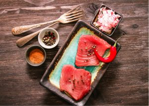 meal kit of raw tuna on plate with condiments and spices on a table