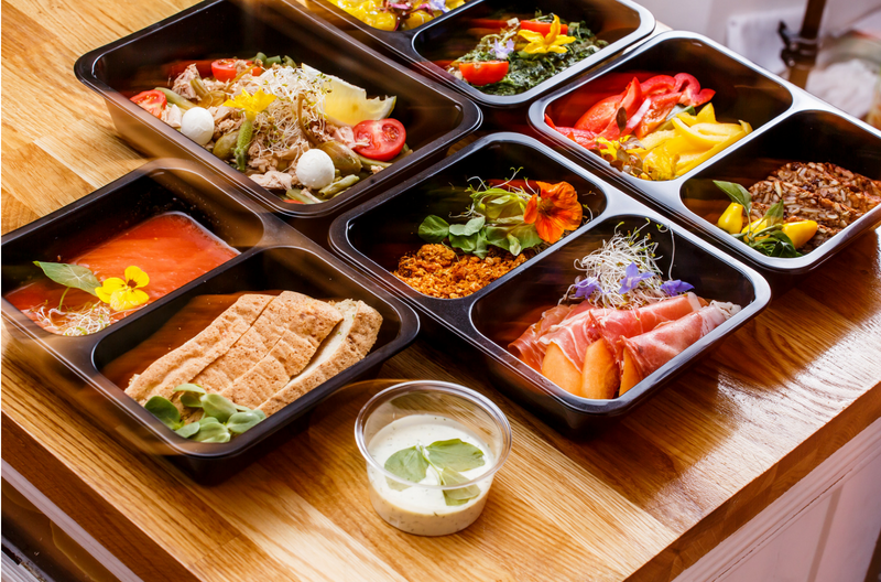 assorted containers from meal prep services on the counter