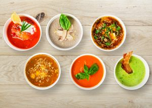 six bowls of healthy colorful soups on a table from meal prep services