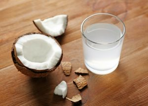 a glass of coconut water and half an open coconut on a table