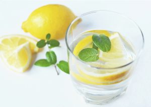 a glass of lemon water with lemon slices