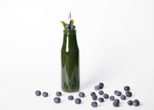 dark green smoothie in a tall bottle with a straw and blueberries