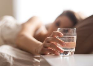 woman in bed reaching for a glass of water