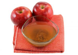 bowl of unfiltered apple cider vinegar including the mother and two red apples