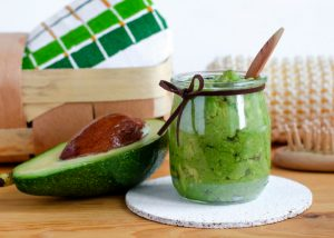 open half of avocado and a jar of natural avocado skin care on a table