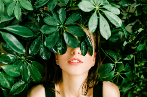 Woman's face covered by green leaves