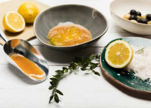honey, lemons, sea salt and olives on a white table