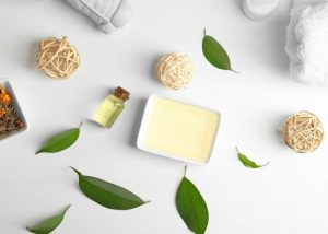 tea tree oil in dish on a white table with leaves and a bottle of organic tea tree beauty product