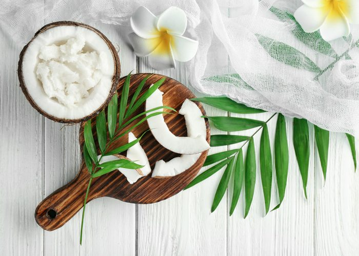 open half of coconut on white table with leaves and flowers