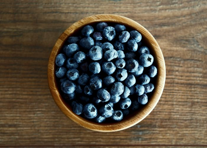 A bowl of fresh blueberries on a wooden table