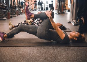 woman stretching her legs at the gym