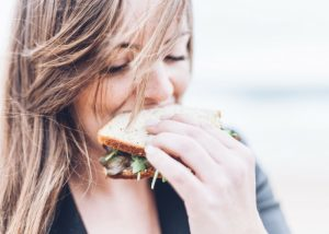 blonde woman biting into a sandwich