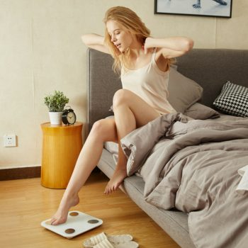 Woman getting out of bed stepping onto a scale