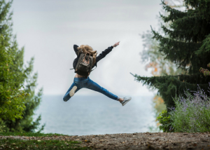 woman jumping while wearing a backpack