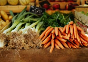 fresh carrots and green onions piled on a cutting board