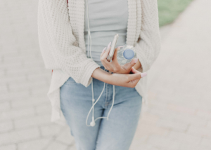 woman walking with a water bottle and cell phone