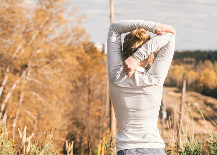 slender woman stretching with one arm behind her head