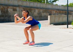 woman doing LIIT body weight squats outside