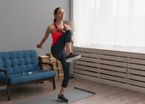 woman doing LIIT knee raises in the living room