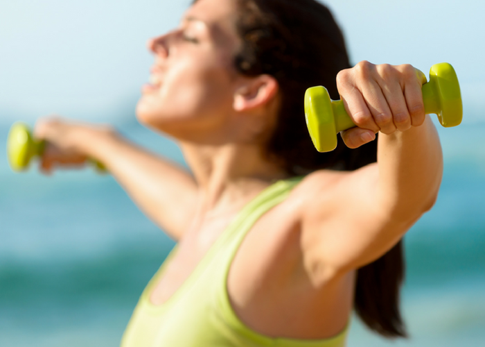 woman in green top holding small dumbbells with raised arms