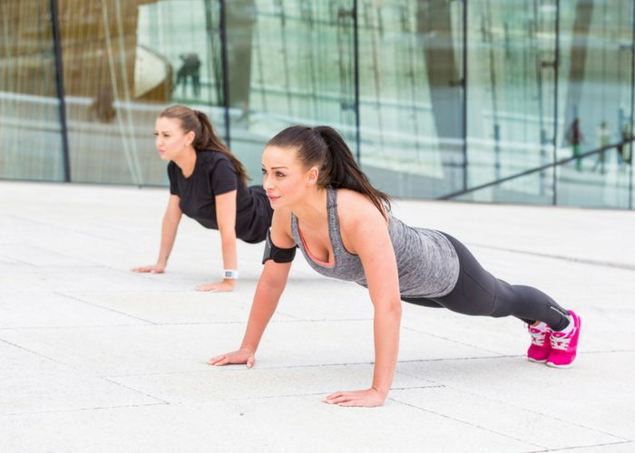 two women doing LIIT plank exercises next to each other
