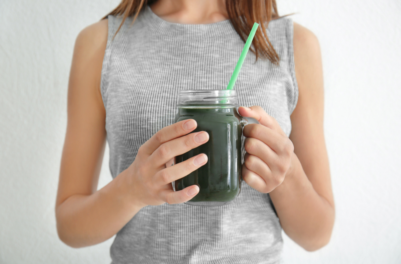 woman holding onto a spirulina smoothie in a mason jar