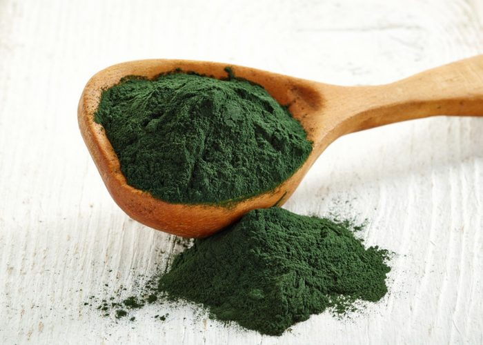 spirulina powder spilling out of a wooden spoon