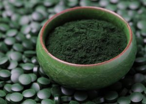 spirulina powder in a dark green bowl surrounded by spirulina tablets