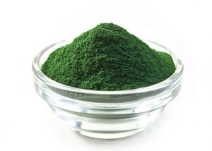 spirulina powder in a small glass bowl on a white background