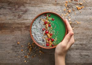 woman's hand holding a spirulina smoothie bowl on a wooden background