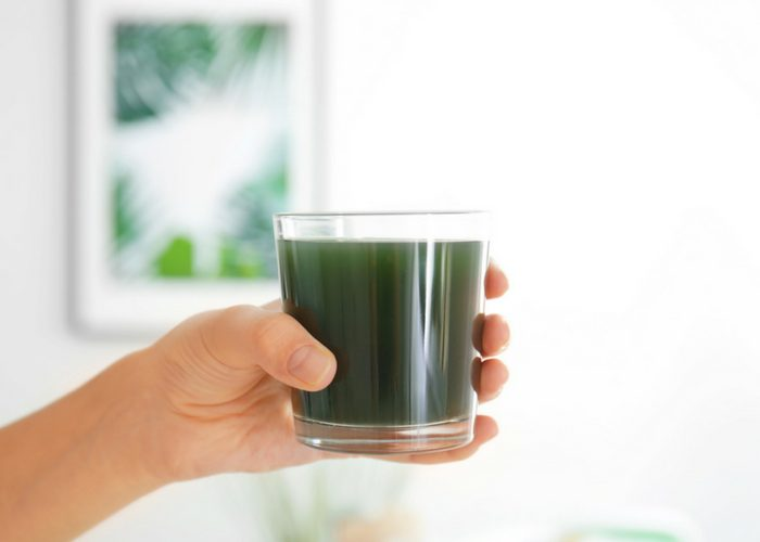 woman's hand holding a glass of spirulina drink