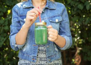 woman in denim jacket holding a mason jar of spirulina smoothie outdoors