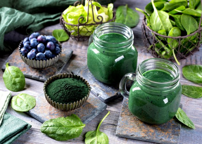 two spirulina smoothies made with anti cancer foods like spinach and blueberries